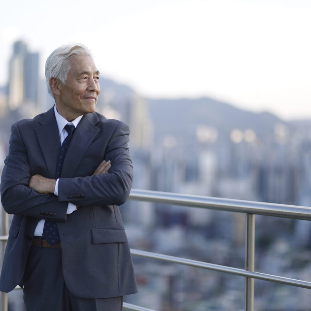 Senior businessman standing with arms crossed on rooftop