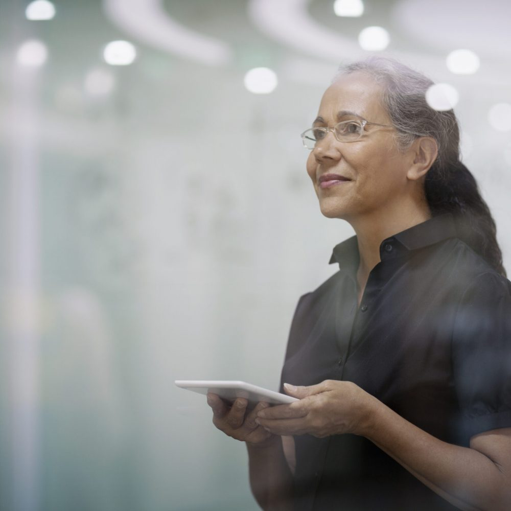 Senior woman with smart tablet computer in office